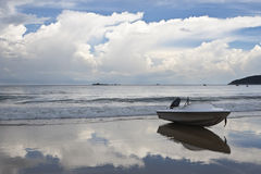 Motorboat on beach. Lone motorboat on the beach with dramatic sky background, sanya, hainan, china stock photography