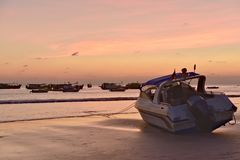 Motorboat on beach during sunset Ngwe Saung Myanmar stock photo