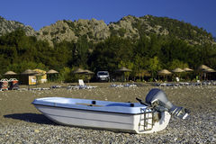 Motorboat on beach and yellow parasols in backdrop. White-blue motorboat on beach and yellow parasols and mountain in backdrop royalty free stock photos