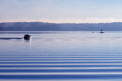 Motorboat on calm cold sea. With beautiful small waves in foreground royalty free stock photos