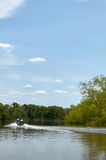 Motorboat on calm river during a bright sunny day. A boat driving on a scenic river leaves a wake on the calm water surface during a bright clear, sunny day in Royalty Free Stock Photos