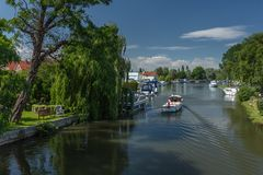 A motorboat cruises towards Beccles Quay on the River Waveney royalty free stock photo