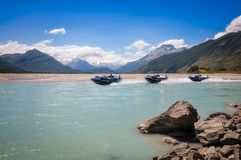 A motorboat on Dart River at Isengard lookout in New Zealand. A motorboat speeding on Dart River with snow-capped mountain view in the background at Isengard Stock Photo