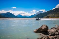 Motorboat drive in the alpine scenery of New Zealand. A motorboat speeding on Dart River with the view of snow-capped mountains in the background at Isengard Royalty Free Stock Image