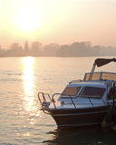 Motorboat in dusk. With sun in background royalty free stock photography