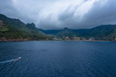 A Motorboat enters a Foggy Harbor. A motorboat enters the harobor of Robinson Crusoe Island in the South Pacific on a foggy day Royalty Free Stock Photo