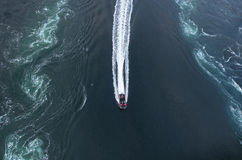 Motorboat between the huge whirlpools Royalty Free Stock Images