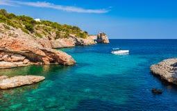 Motorboat at idyllic bay coast landscape of Majorca island. Luxury motor yacht boat at the coast on Mallorca island, Spain Mediterranean Sea royalty free stock image