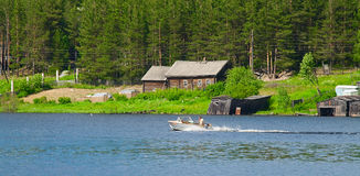 Motorboat on lake. Motorboat on water and evergreen forest on back. Countryside Stock Photos