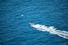 A small motorboat rides on the water stock photography