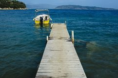 Motorboat moored to a wooden pier on the bottom there are islands in the sea there is none. Motorboat moored to a wooden pier on the bottom there are islands, in royalty free stock photography