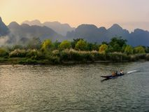 Motorboat moving on Nam Song River at susnet in Vang Vieng, Vien. Motorboat moving on Nam Song River at sunset in Vang Vieng, Laos. Vang Vieng is a popular Stock Image