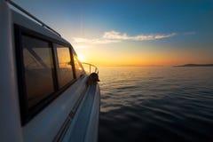 Motorboat moving to sunset. White motorboat moving to sunset royalty free stock photo