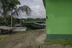 Motorboat parked at the riverbank. A green parked boat at the riverbank just around a corner stock photo