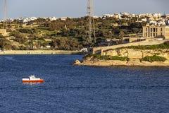 A motorboat passes along the Kalkara coastline, Rinella Bay Kalkara Malta. A red and white motorboat passes along the Kalkara coastline, Rinella Bay Kalkara Stock Images