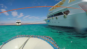 Motorboat passes by pleasure boat. The view from motorboat stock footage