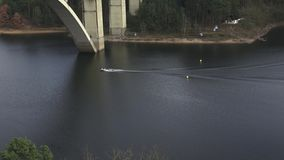 Motorboat passing under concrete bridge. Concrete bridge over river. stock video footage