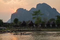 Scenic landscape in Vang Vieng, Laos at sunset. Motorboat passing by a waterfront restaurant and bungalows by the the Nam Song River in Vang Vieng, Vientiane stock image