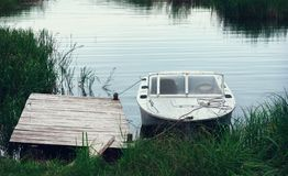 Motorboat At The Pier Among The reeds In A River Bay. An old metal skiff is moored to a wooden pier in a small river bay among the reeds in the countryside royalty free stock photos