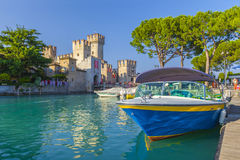Motorboat at port Sirmione in front of castello Scaligero at lake Garda. Brescia, Lombardy, Italy Royalty Free Stock Photo