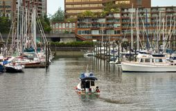 A motorboat pulling into a marina in a residential part of vancouver`s port royalty free stock image