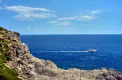 Motorboat on the rocky coast Stock Photo