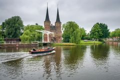 Motorboat sails at the canals of Delft, Netherlands. Delft, Netherlands - June 2, 2018 : Motorboat sails at the old canals of Delft with eastern gate in the stock images