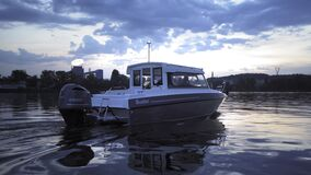 Motorboat is slowly sailing on the Dnipro. Evening skies and a little cloudiness in the background. High quality 4k