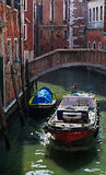 Motorboat on a Small Venetian Canal. Venice, Italy- February 25th, 2011: Image of a motorboat on a small Venetian canal carrying packages royalty free stock images