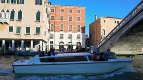 Motorboat with tourists sailing on canal in Venice, view on bridge and buildings stock video footage