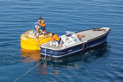 Motorboat is used for rope attachment on mooring buoy Royalty Free Stock Photos