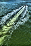 Motorboat wake in water. Motorboat leaves long diagonal wake in water Stock Photography
