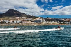 Motorboating in the deep-blue waters off the west coast of Tenerife, one of many leisure activities offered to tourists in the Can. Motorboating off the west stock photography