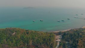Motorboats drift on calm ocean water at beach aerial view. White motorboats drift on calm ocean water near forestry coastline and sand beach with island on stock video footage