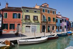 Motorboats moored along the water canal of island Burano in Italy. There are some beautiful houses are stand on the fastening Stock Photography