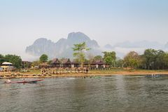 Motorboats on the Nam Song River in Vang Vieng, Laos. Three motorboats with tourists passing by a waterfront restaurant and bungalows by the the Nam Song River royalty free stock images