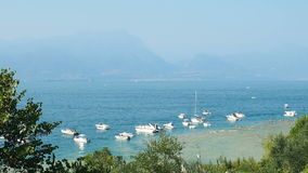 Motorboats and yacht at bay Sirmione Lake Garda. Sirmione, Italy - August 2016: motorboats and yacht at bay stock footage