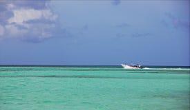 Motorboot die in de mooie tropische oceaan, tegen de blauwe grenzeloze hemel vaart stock afbeelding