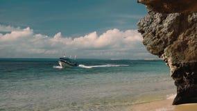 Motorboot die dichtbij wit zandstrand overgaan met klip stock videobeelden