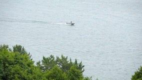 Motorboot die door lakeshore op een de zomerdag kruisen stock footage