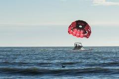 Motorboot die een parasailvalscherm met een opgeschorte binnen persoon slepen Stock Afbeeldingen