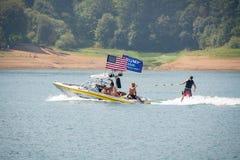 Motorboot met de vlaggen van Amerikaan en van de pro-troef op het meer stock fotografie
