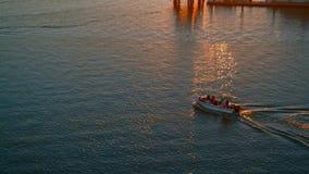 Motorboot met passagiers op een rivier bij schitterende zonsondergang stock video