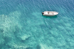 Motorboot in ondiep turkoois water wordt verankerd dat royalty-vrije stock fotografie
