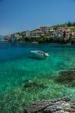 Motorboot in turkooise baai in Kephalonia met huizen op t wordt vastgelegd dat Stock Afbeeldingen