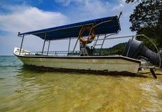 Motorboot verankert nahe dem Strand am sonnigen Tag Lizenzfreie Stockfotografie