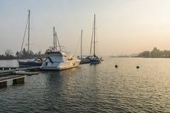 Motorboote und Segelboote am Pier auf dem See Stockfotografie