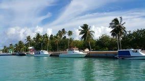 Motorboten op een turkooise lagune, dichtbij de pier van Kudahuvadhoo-eiland met palmtrees Stock Foto's