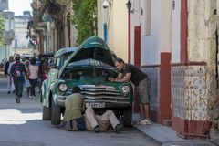 Mechanics try to repair classical car in street of Havana. Motorcar mechanics repair classical american car in small street of old town - La Havana Vieja Stock Photography