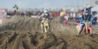 Motorcross competition. Focus on the sand. Panorama size Royalty Free Stock Image
